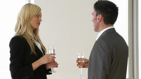 Businesswoman and businessman celebrating a success with champagne. Footage of a businesswoman and businessman celebrating a success with champagne in office stock video