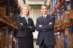 Businesswoman And Businessman In Distribution Warehouse. Looking to camera royalty free stock photo