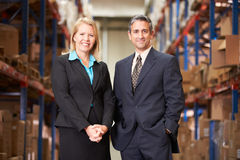 Businesswoman And Businessman In Distribution Warehouse. Looking to camera stock photography