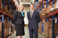 Businesswoman And Businessman In Distribution Warehouse. Smiling To Camera royalty free stock image