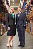 Businesswoman And Businessman In Distribution Warehouse. Smiling To Camera stock photography