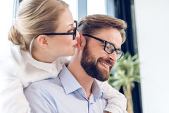 Businesswoman and businessman with eyeglasses hugging and working with laptop Stock Photography