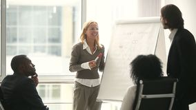 Businesswoman and businessman giving presentation using flipchart, discussing new strategy. Businesswoman and businessman giving presentation using flipchart stock footage