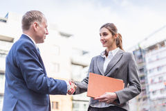 Businesswoman and businessman make a deal outdoor Stock Image