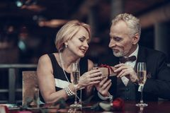 Woman accepts gift from Businessman in Restaurant royalty free stock images