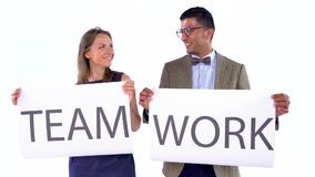 Two business partners posing in the studio with placards in hands. The concept of teamwork. Businesswoman and businessman posing in the studio with placards in stock video footage