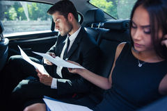 Businesswoman and businessman reading papers in car Royalty Free Stock Photo