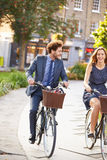 Businesswoman And Businessman Riding Bike Through City Park Royalty Free Stock Images