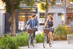 Businesswoman And Businessman Riding Bike Through City Park. Smiling At Each Other