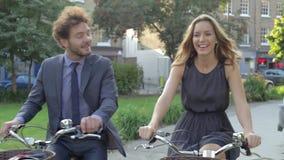 Businesswoman And Businessman Riding Bike Through City Park stock footage