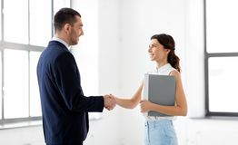 Businesswoman and businessman shake hands. Business people, partnership and cooperation concept - happy smiling businesswoman with folder and businessman shake Stock Images