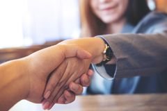 Businesswoman and businessman shaking hand to each other in office stock images