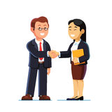 Businesswoman and businessman shaking hands. Businesswoman and man standing and shaking hands. Successful business deal or agreement. Collaboration concept Stock Photography