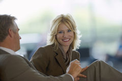 Businesswoman and businessman sitting in waiting area, smiling, side view, portrait Royalty Free Stock Image
