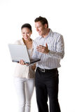 A businesswoman and businessman smile happily. A businesswoman and businessman get their mind focused on an important document from their notebook Stock Photography