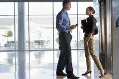 Businesswoman and businessman standing beside elevator in lobby, face to face, talking, profile Stock Image