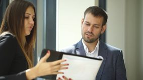 Businesswoman and businessman standing in office and discussing business ideas. Businesswoman and businessman standing in office near Windows and discuss stock video