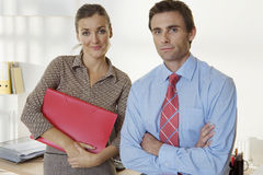 Businesswoman and businessman standing in office, smiling, front view, portrait Stock Photos