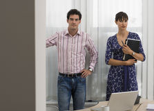 Businesswoman and businessman standing in office, woman holding folder, smiling, portrait Royalty Free Stock Photo