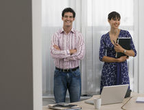 Businesswoman and businessman standing in office, woman holding folder, smiling, portrait Royalty Free Stock Photography