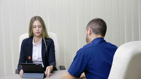 Businesswoman and businessman talking in the office. Woman is showing something on a digital tablet stock video footage
