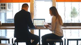 Businesswoman and businessman using laptop in cafe. And discuss business plans stock footage
