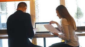 Businesswoman and businessman using laptop in cafe and discuss business plans. Two coworkers discussing work project while on lunch break in cafeteria stock video