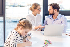 Businesswoman and businessman working with laptop in office with little daughter drawing on foreground Royalty Free Stock Photography