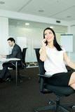 Businesswoman and a businessman working in an office  while sitt Stock Photo