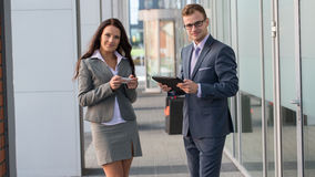 Businesswoman and businessman working outside with mobile phone and tablet pc. Royalty Free Stock Images