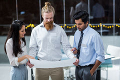 Businesswoman and businessmen discussing over blueprint Stock Photo