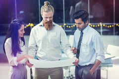 Businesswoman and businessmen discussing over blueprint Stock Photography