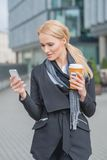 Businesswoman Busy with Phone While Having Coffee Stock Image