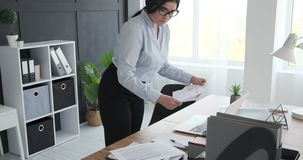 Businesswoman busy working at office. Businesswoman using laptop and doing paperwork at office stock footage