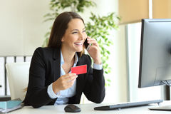 Businesswoman buying online and calling customer service. Happy businesswoman working buying on line with credit card and calling customer service at office Stock Image
