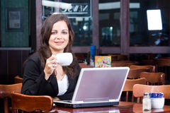Businesswoman in cafe. A young smart businesswoman working on laptop computer in a cafe Royalty Free Stock Image