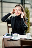 Businesswoman in a cafe on the street. Woman in a cafe on the street, with a cup of coffee sitting at a desk and talking on the phone Royalty Free Stock Image
