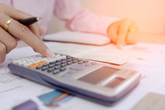 Businesswoman calculate about cost and charts report on table, calculator on desk of financial planing. Finance concepts. Royalty Free Stock Photos