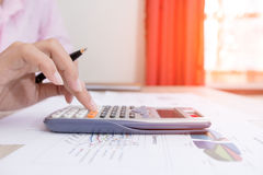 Businesswoman calculate about cost and charts report on table, calculator on desk of financial planing. Finance concepts. Businesswoman calculate about cost and Royalty Free Stock Photos