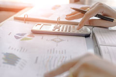 Businesswoman calculate about cost and charts report on table, calculator on desk of financial planing. Finance concepts. Businesswoman calculate about cost and Royalty Free Stock Images