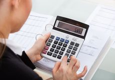 Businesswoman calculating bills Stock Images