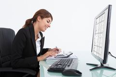 Businesswoman calculating bills at desk Stock Image