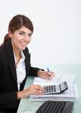 Businesswoman calculating bills at desk Stock Photo