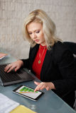 Businesswoman calculating insurance in office Stock Image
