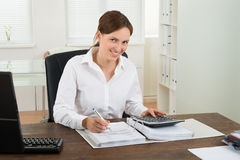 Businesswoman Calculating Invoice Royalty Free Stock Images