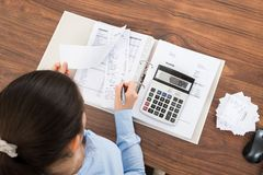 Businesswoman calculating tax at desk Stock Images