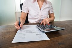 Businesswoman Calculating Tax At Desk Royalty Free Stock Images