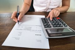 Businesswoman Calculating Tax At Desk royalty free stock image