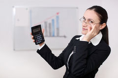 A businesswoman with calculator. A businesswoman is holding a calculator in a conference room Stock Images