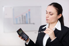 Businesswoman with calculator. A businesswoman is holding a calculator in a conference room Royalty Free Stock Photos